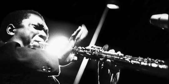 John Coltrane performs on stage at the Half Note club, New York, 1965. (Photo by Adam Ritchie/Redferns)